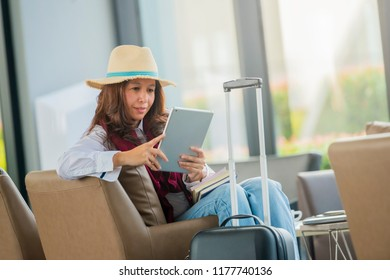 Asian woman passenger at the airport using her tablet for checking her flight details with wifi connection while waiting for flight.