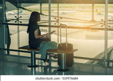 Asian woman passenger at the airport, using her tablet computer while waiting for her flight and background blur airplane, view from airport terminal. (vintage color tone, lens blur effect)