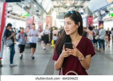 Asian woman passenger with casual suit using the smart mobile phone in the train rails or subway for travel in the big city, lifestyle and transportation concept