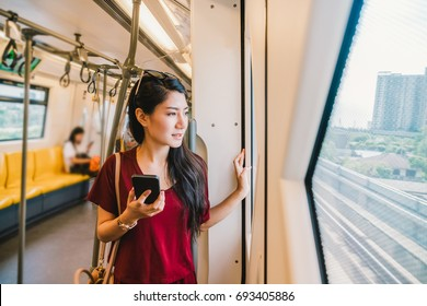 Asian woman passenger with casual suit using smart mobile phone in the Skytrain rails or subway for travel in the big city, lifestyle and transportation concept