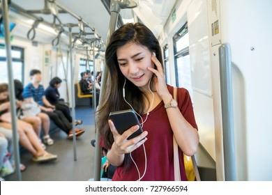Asian woman passenger with casual suit using and listening the song via smart mobile phone in the Skytrain rails or subway for travel in the big city, lifestyle and transportation concept