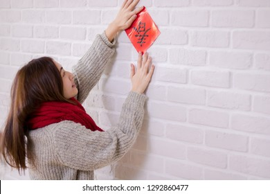 Asian woman pastes red couplet on the wall in Chinese new year. The Chinese text on the couplet means Spring.