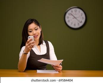 An asian woman paying bills online using a smartphone