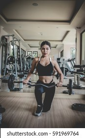 Asian woman performing deadlift exercise with weight bar. Confident young woman doing weight lifting workout at gym.fitness girl concept