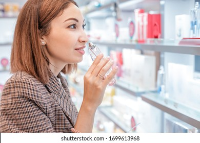 Asian woman in a perfume store tests and sniffs a new perfume fragrance. Concept of business in cosmetic shop