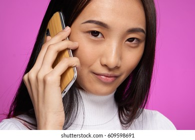 Asian woman with phone in hand, talking on phone