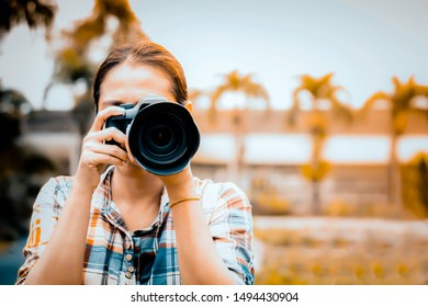 Asian woman photographer is taking images with digital camera on nature background