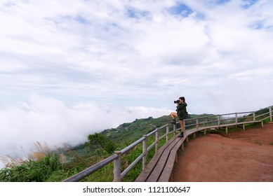 Asian Woman Photographers are shooting the mist in morning. Travel Concept.