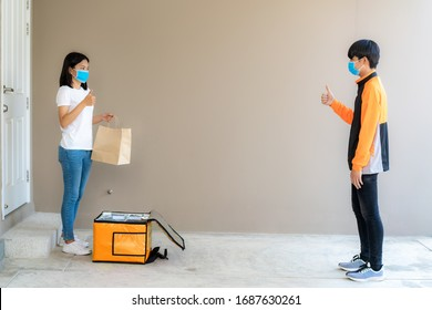 Asian woman pick up delivery food bag from box and thumb up form contactless or contact free from delivery rider with bicycle in front house for social distancing for infection risk.