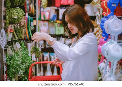 Asian woman picking up artificial green plant for home decoration at retail shop