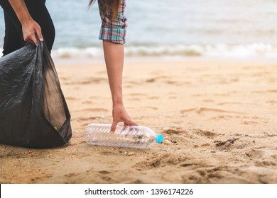 Asian woman picking  bottle into plastic bag black for cleaning the beach in morning time, Volunteer concept.