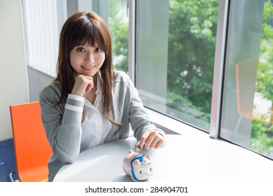 Asian woman with piggy bank