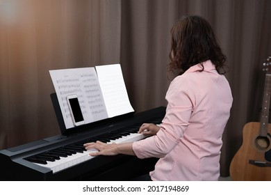 An asian woman in pink shirt and short spiral hair playing paino at home, smartphone and key note and blank paper on paino holder. relaxing time with music instrument. Professional musicain.
