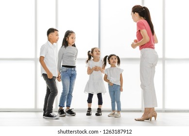 Asian woman in pink shirt teach Asian girls and boy some acting to act fake cry, they stand in front of big white window.