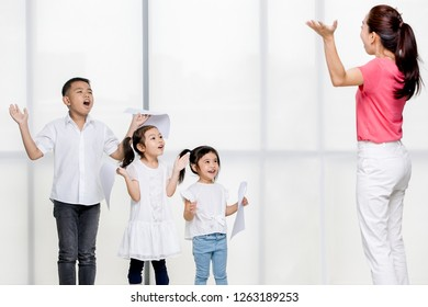 Asian woman in pink shirt teach Asian girls and boy utter, they stand in front of big white window.