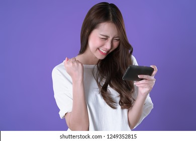Asian woman play mobile game on smartphone and win, white t-shirt clothing, purple background