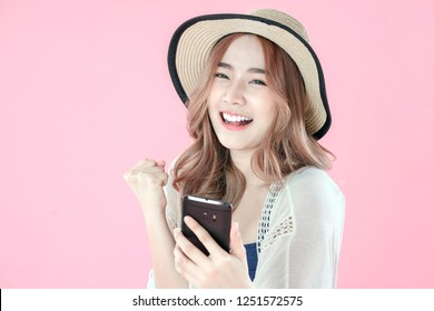 Asian woman play mobile game on smartphone and win, summer holiday clothing, pink background