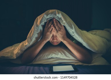 Asian woman play smartphone in the bed at night,Thailand people,Addict social media,Play internet all night