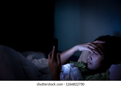 Asian woman play smartphone in the bed at night,Thailand people,Addict social media,Play internet all night,Lychnobite