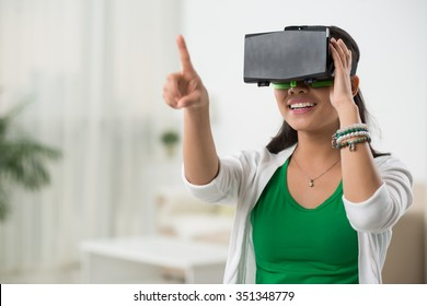 Asian woman playing game in virtual reality glasses