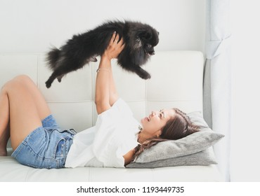 Asian woman playing with little dog black color in living room lifestyle girl with pet