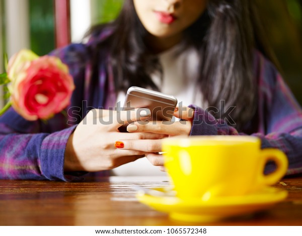 asian woman playing with mobile phone while drinking coffee cappuccino, focus on hands.