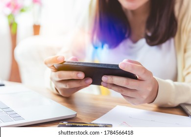 Asian woman playing online game application or chatting text message with friend by using smart phone. Danger of blue light can damage eyes and can be age related macular degeneration from blue light