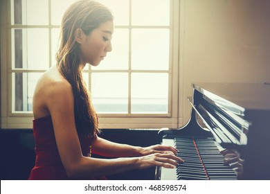 Asian woman playing piano in window background with light coming in (Vintage tone)