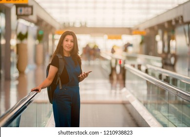 Asian woman playing smartphone in the moving walkway at the airport with backpack.