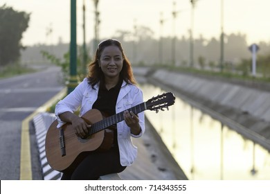 an asian woman plays guitar in the park in the morning