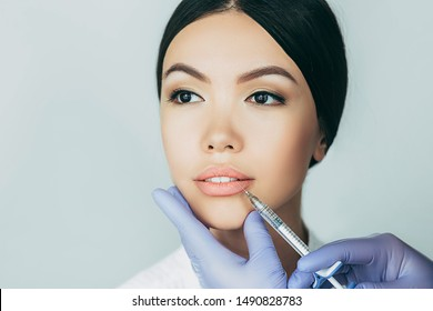 asian woman plumper lips, getting bigger lips. prick of a syringe for the lips. injections for bigger volume