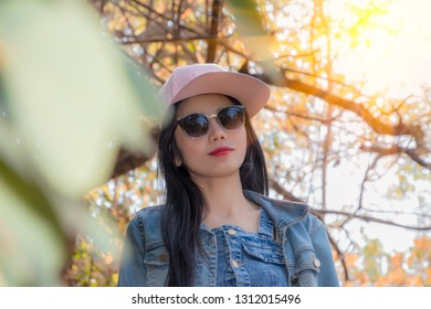 Asian woman portrait of Beautiful girl in blue jeans jacket glasses and pink hat standing near colorful autumn leaves. Pretty model looking and smiling at camera at sunset time. Romantic woman.