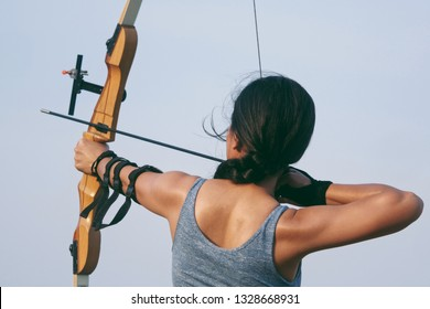 Asian woman portrait with bow archery concept on the beach