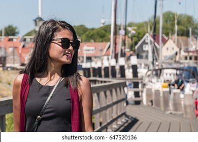 Asian woman portrait walking at the harbor of Urk boulevard, young happy asian woman at a wooden pier with sailing boats on the background