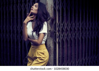 An Asian woman posing for a portrait shoot in front of an old townhouse in Talad noi, old community, Bangkok, Thailand