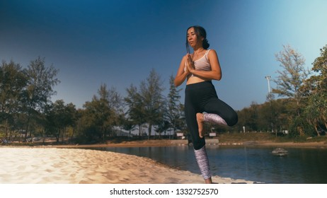Asian woman practice yoga fitness exercise on the beach. Healthy lifestyle.