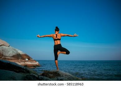 Asian woman practice yoga on the beach blue sky