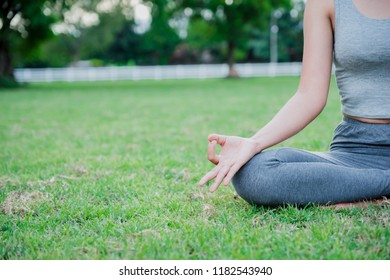 Asian woman practices yoga and meditates on meadow in the park.