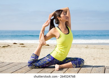Asian woman practicing yoga at boardwalk seashore