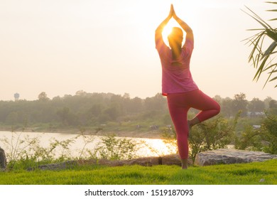 Asian woman practicing yoga in a garden. Healthy lifestyle and relaxation concept