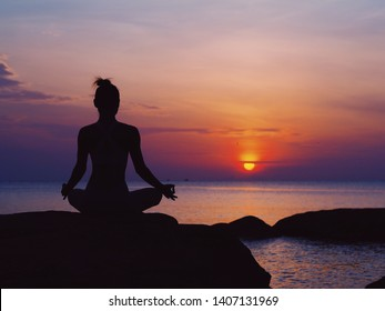 Asian woman practicing yoga pose on the beach at sunset time.