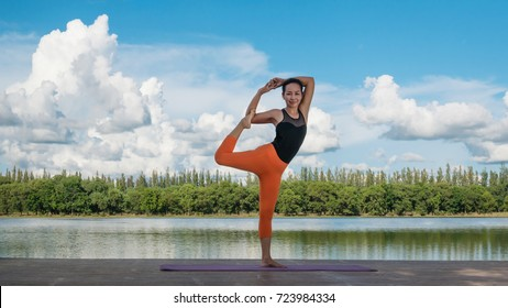 Asian woman practicing yoga pose , exercise outdoors with view of beautiful lake - relax in nature