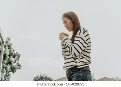 Asian woman praying and believe in God, christian study concept.