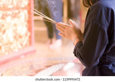 Asian woman praying with incense sticks in Chinese temple, Buddhism religion