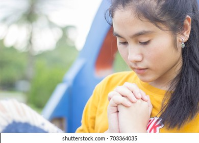 Asian woman praying on holy bible. teenager asian woman hand with bible praying. hands folding in prayer on holy bible in church concept for faith, spirituality and religion.