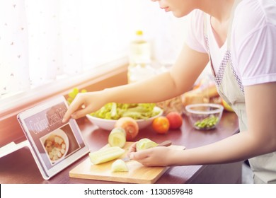 Asian woman prepare ingredients for cooking follow cooking class online course on website via tablet. cooking content on internet technology for modern lifestyle concept