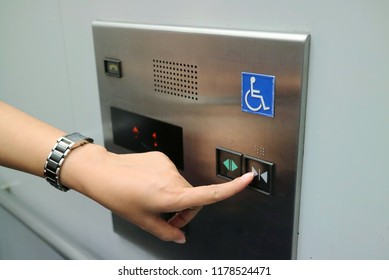 Asian woman pressing the disabled elevator button of the elevator. Soft focus. Technology and sign concept.
