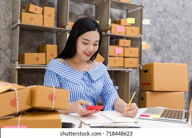 Asian woman with product packaging work at home concept, small and medium-sized enterprises (SMEs) concept.