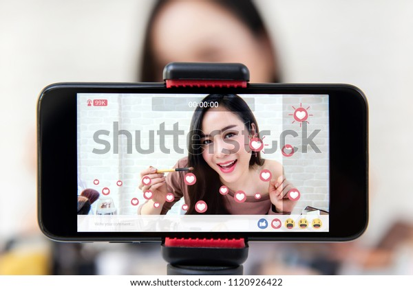 Asian woman professional beauty vlogger or blogger live broadcasting cosmetic makeup tutorial viral video clip by smartphone sharing on social media