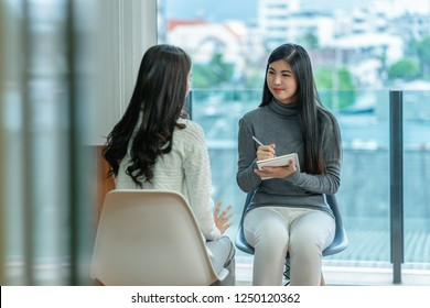 Asian woman professional psychologist doctor giving the consult to female patients in modern living room of house or hospital exam room, Mental health Concept